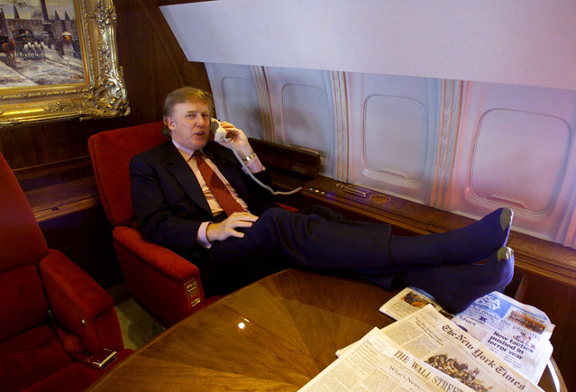 Potential Reform Party presidential candidate Donald Trump uses the phone and puts his sock-covered feet on the table in his private plane as he flies to Minnesota for a speech and to attend a fund-raiser for Gov. Jesse Ventura, Friday January 7, 2000. (Photo by AP Photo)