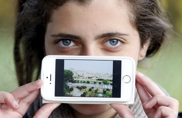 Migrant Haya from Artoz, Syria, shows a picture of her town as she waits to cross the Slovenia-Austria border in Sentilj, Slovenia October 25, 2015. (Photo by Srdjan Zivulovic/Reuters)