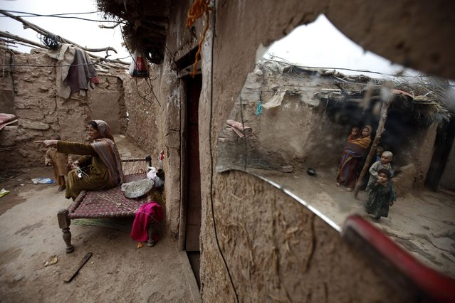A woman talks to her children at her house in a slum on the outskirts of Islamabad March 20, 2013. (Photo by Zohra Bensemra/Reuters)