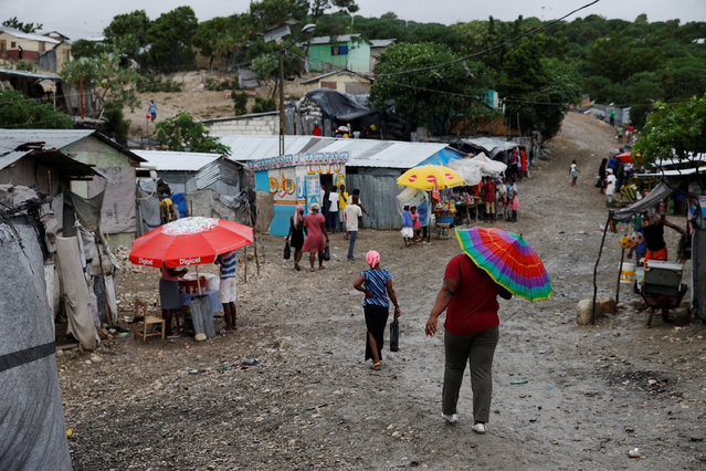 People walk down the street at a camp for displaced people while Hurricane Matthew approaches in Port-au-Prince, Haiti October 3, 2016. (Photo by Carlos Garcia Rawlins/Reuters)