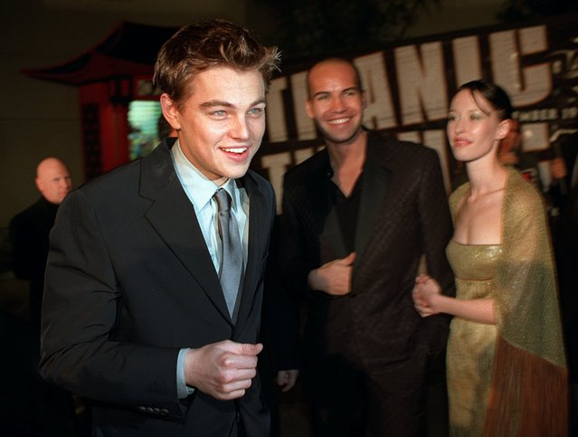 """""""Titanic"""" star Leonardo DiCaprio, left, walks past fellow cast member Billy Zane, center, as he arrives for the premiere of the film Sunday, December 14, 1997, at the Mann's Chinese Theater in the Hollywood section of Los Angeles. Accompanying Zane is Jessica Murphy. (Photo by Rene Macura/AP Photo)"""