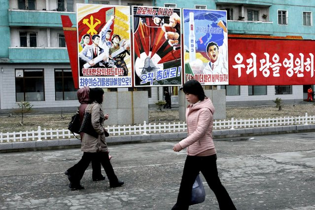 "North Koreans walk past posters reading ""Forward to the ultimate victory under the leadership of the great party!"" left, ""Not with words but with arms"", center, and ""Higher, faster"", right, on Tuesday, March 19, 2013, on a street in Phyongchon District in Pyongyang, North Korea. The banner partially shown at right reads in its entirety ""Let's strengthen and enhance our party as the party of Kim Il Sung and Kim Jong Il!"" (Photo by Jon Chol Jin/AP Photo)"