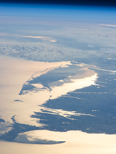 The coastline of the northeastern U.S., observed from the ISS on February 14, 2013. The Atlantic Ocean, including Cape Cod Bay and Buzzards Bay along the coastlines of the states of Massachusetts and Rhode Island has a burnished, mirror-like appearance in this image. This is due to sunlight reflected off the water surface back towards the astronaut-photographer. The peak reflection point is towards the right side of the image, lending the waters of Long Island Sound (at image center, to the north of Long Island) and the upper Massachusetts coastline an even brighter appearance. Sunglint also illuminates surface waters of Chesapeake Bay (top center) located over 400 km to the southwest of the tip of Long Island. The high viewing angle from the ISS also allows the Earth's curvature, or limb, to be seen, and blue atmospheric layers gradually fade into the darkness of space across the top part of the image. (Photo by NASA/The Atlantic)