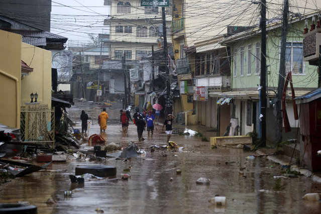 Filipino residents walk in a flooded street after Typhoon Hagupit made landfall, in Borongan city, Samar island, Philippines, 07 December 2014. Typhoon Hagupit knocked out power and flattened houses as it pummelled the eastern and central Philippines overnight, leaving millions of people in darkness amid heavy rains and howling winds, officials said. At least three people were killed and two injured as powerful typhoon lashed the eastern and central Philippines. (Photo by Francis R. Malasig/EPA)