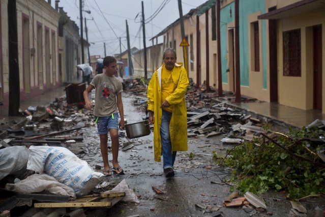 Residents carry food down a street strewn with rubble caused by Hurricane Matthew in Baracoa, Cuba, Wednesday, October 5, 2016. (Photo by Ramon Espinosa/AP Photo)