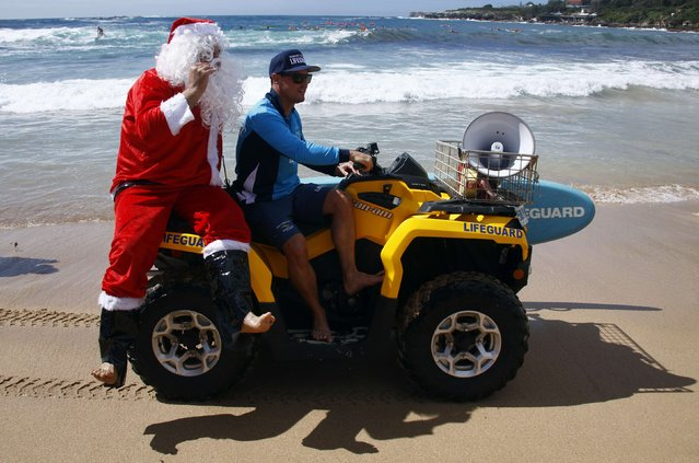 A man dressed as Santa Claus is driven on a quad-bike by a lifesaver after arriving in an inflatable rescue boat (IRB), as part of Christmas celebrations for the Coogee Surf Lifesaving Club, at Sydney's Coogee Beach December 14, 2014. (Photo by David Gray/Reuters)