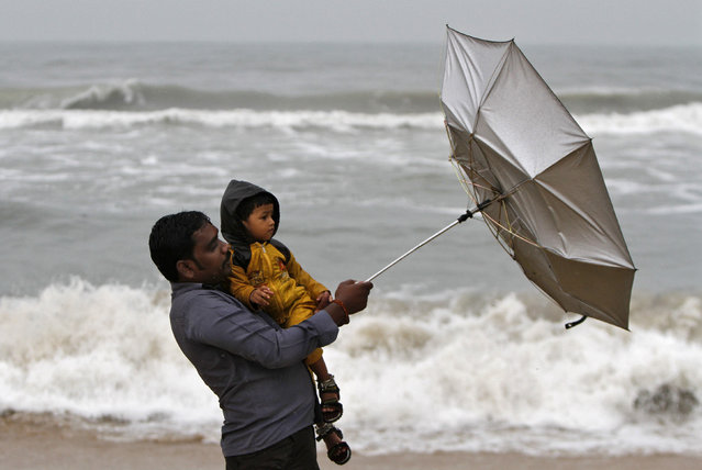 A man carrying his child tries to hold an umbrella at Marina beach in the southern Indian city of Chennai October 30, 2012. (Photo by Reuters/Babu)