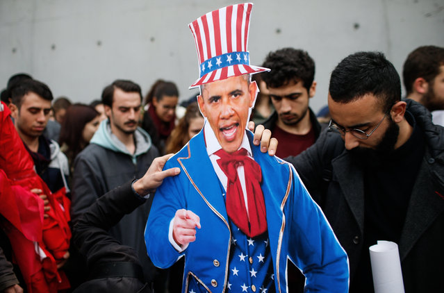 Plainclothes police officers take away an effigy of US President Barack Obama as the members of Turkey Youth Union gather to protest against the upcoming visit of Obama to Turkey mid-November for G20 summit in Antalya, outside the US consulate in Istanbul, Turkey, Sunday, November 8, 2015. (Photo by Emrah Gurel/AP Photo)