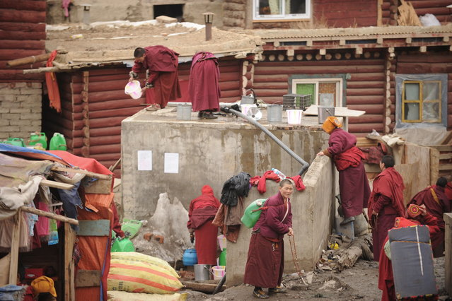 This photo taken on April 4, 2013 shows apprentice Buddhist monks and nuns collecting water in Seda Monastery, the largest Tibetan Buddhist school in the world, with up to 40,000 monks and nuns in residence for some parts of the year. Seda, known to Tibetans as Serthar is located in Ganzi prefecture in the west of China's Sichuan province and has become a hotbed of protests and violence since the Tibetan uprisings of March 2008. (Photo by Peter Parks/AFP Photo)