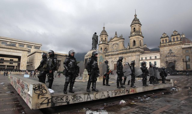 Riot police stand guard in Bolivar square after the annual May Day march ended in clashes in Bogota, Colombia, Wednesday, May 1, 2013. In protests, parades, strikes and other demonstrations held in cities across the planet, activists lashed out at political and business leaders they allege have ignored workers' voices or enriched themselves at the expense of laborers during what has been a difficult few years for the global economy. (Photo by Fernando Vergara/AP Photo)