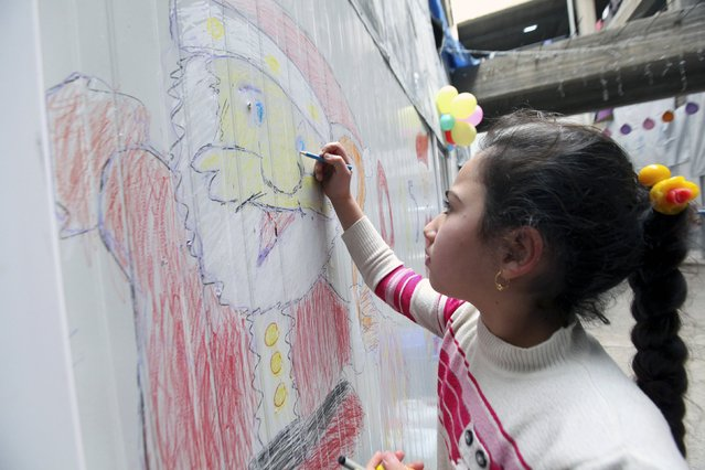 A displaced Iraqi Christian girl who fled from Islamic State militants in Mosul,  draws a picture of Santa Claus at a mall still under construction, used as a refugee camp in Arbil December 24, 2014. (Photo by Azad Lashkari/Reuters)