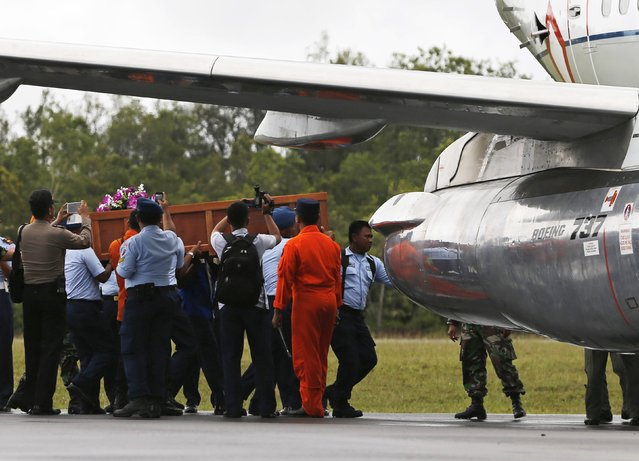 Air Force soldiers carry a coffin containing the body of a passenger onboard AirAsia flight QZ8501 at Iskandar airbase in Pangkalan Bun district, Indonesia, to be transported to Surabaya, December 31, 2014. A body recovered on Wednesday from the crashed AirAsia plane was wearing a life jacket, an official with Indonesia's search and rescue agency said, raising questions about how the disaster unfolded. (Photo by Reuters/Beawiharta)