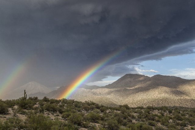 Two rainbows emerge from a black storm above the mountains, on August 19, 2014, in Kingman, Arizona. (Photo by Roger Hill/Barcroft Media)
