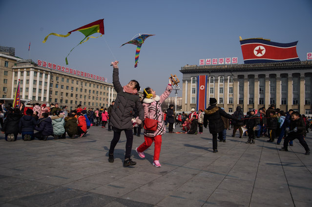 Children fly kites during Lunar New Year festivities on Kim Il Sung square in Pyongyang on February 16, 2018. (Photo by Kim Won-Jin/AFP Photo)