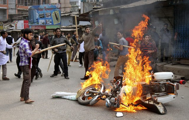 Bangladesh Nationalist Party and Jamaat-e-Islami party activists set fire to a police motorbike in Dhaka, Bangladesh, Monday, January 5, 2015. Two men on a motorbike opened fire on a group of anti-government activists in northwestern Bangladesh on Monday, killing two amid heightened tensions on the anniversary of a general election boycotted by a major opposition alliance last year, a local opposition leader said. (Photo by S.K. Hasan Ali/AP Photo)