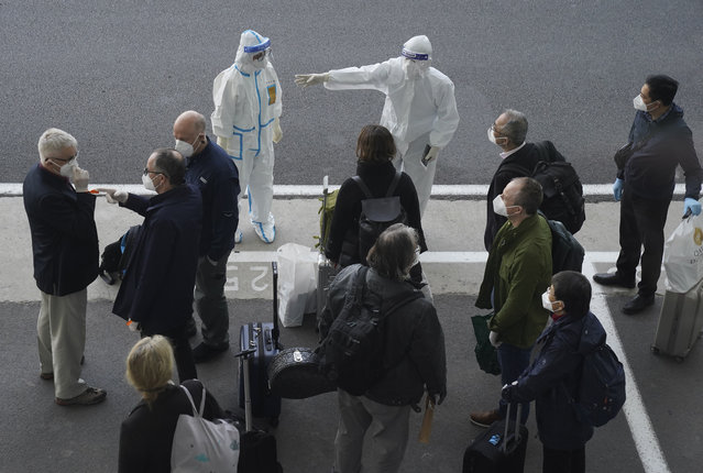 A worker in protective coverings directs members of the World Health Organization (WHO) team on their arrival at the airport in Wuhan in central China's Hubei province on Thursday, January 14, 2021. A global team of researchers arrived Thursday in the Chinese city where the coronavirus pandemic was first detected to conduct a politically sensitive investigation into its origins amid uncertainty about whether Beijing might try to prevent embarrassing discoveries. (Photo by Ng Han Guan/AP Photo)