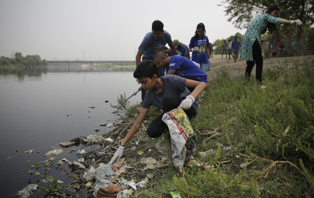 Volunteers clean the banks of Yamuna, India's sacred river that flows through New Delhi, Tuesday, June 5, 2018. (Photo by Altaf Qadri/AP Photo)
