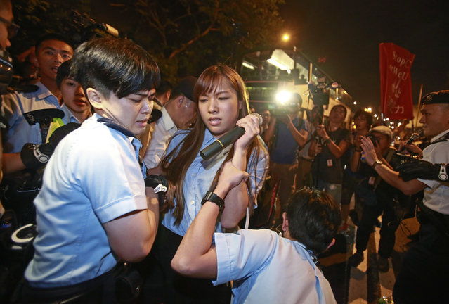 Newly elected Hong Kong lawmakes Yau Wai-ching, second left, scuffles with police officers after clashing as thousands of people march in a Hong Kong street, Sunday, November 6, 2016. Thousands of protesters marched in Hong Kong on Sunday, demanding that China's central government stay out of a political dispute in the southern Chinese city after Beijing indicated that it would intervene to deter pro-independence advocates. (Photo by Kin Cheung/AP Photo)