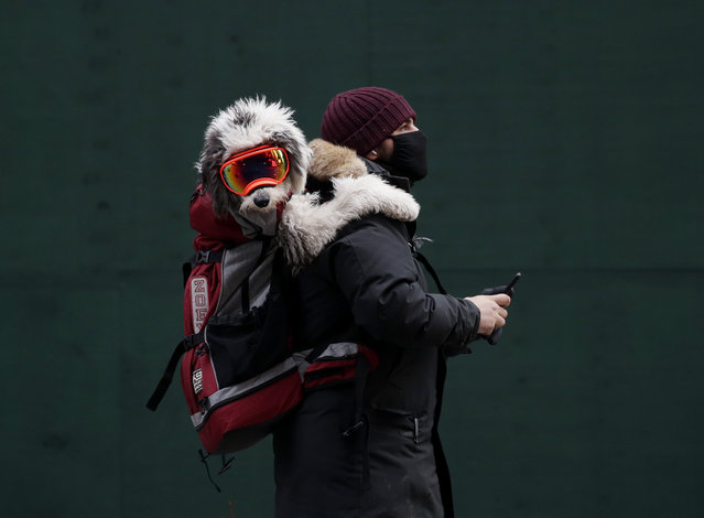 A dog wearing ski goggles rides on the back of a man as they both stand in Times Square in New York, USA on January 25, 2021. (Photo by John Angelillo/UPI/Rex Features/Shutterstock)