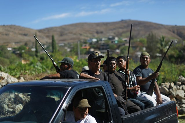 Members of the Community Police of the FUSDEG (United Front for the Security and Development of the State of Guerrero) ride with their weapons in the back of a truck to a celebration to mark the first anniversary of the force's operations in Ocotito, January 23, 2015. (Photo by Jorge Dan Lopez/Reuters)