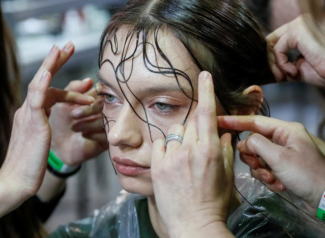 A model has her make-up applied backstage at the Ukrainian Fashion Week in Kyiv, Ukraine on February 5, 2021. (Photo by Gleb Garanich/Reuters)