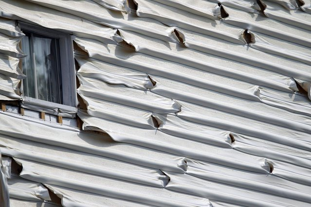 Melted siding on a home is seen near the scene of a train derailment in Lac Megantic, Quebec, July 7, 2013. (Photo by Christinne Muschi/Reuters)