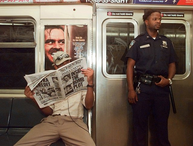 """A subway rider reads a newspaper while on the """"B"""" train in the Brooklyn borough of New York Saturday, August 2, 1997. Security has been increased on New York's subways following the arrest of two men suspected of a subway bombing plot. (Photo by Adam Nadel/AP Photo)"""