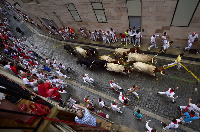 Revellers run next to Puerto de San Lorenzo's fighting bulls during the running of the bulls at the San Fermin Festival, in Pamplona, northern Spain, Saturday, July 7, 2018. (Photo by Alvaro Barrientos/AP Photo)