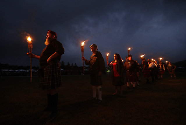Members of various Scottish clans stand with torches as they prepare to announce their arrival during the opening ceremony for the 63rd Annual Grandfather Mountain Highland Games in Linville, N.C., Thursday, July 12, 2018. (Photo by Chuck Burton/AP Photo)