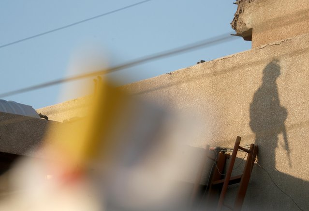 A shadow of a member of Iraqi security forces is seen on a wall before Pope Francis arrival to hold a Mass at Chaldean Cathedral of Saint Joseph in Baghdad, Iraq, March 6, 2021. (Photo by Yara Nardi/Reuters)