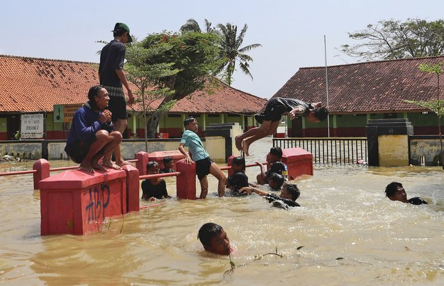 Indonesian youths play in the water during a flood in Bekasi, Indonesia, Monday, February 22, 2021. Thousands of residents are being evacuated on the outskirts of Indonesia's capital amid flooding after the Citarum River embankment broke, officials said Monday. (Photo by Achmad Ibrahim/AP Photo)
