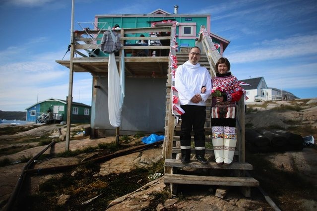 On the day of their wedding, Ottilie Olsen and Adam Olsen (left) pose for a picture in Qeqertaq, Greenland, on July 20, 2013. (Photo by Joe Raedle/Getty Images via The Atlantic)