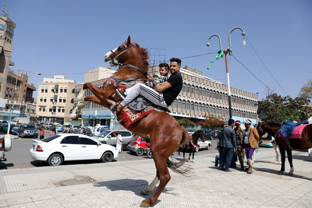A man and his son ride a horse at Tahrir Square in Sanaa, Yemen on January 21, 2021. (Photo by Khaled Abdullah/Reuters)
