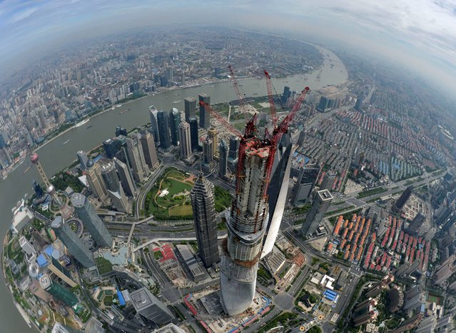 This photo taken Saturday, August 3, 2013, shows an aerial view of Shanghai Tower after a final beam is installed in Shanghai, China. A topping-out ceremony was held Saturday for China's tallest building in the financial hub of Shanghai when the final beam was hoisted to the top of the skyscraper and installed in a flag-waving ritual. At 632 meters (2,073 feet), the Shanghai Tower in the city's Pudong district is the world's second-tallest building, surpassed only by Dubai's Burj Khalifa, which soars 829.8 meters (2,722 feet). (Photo by AP Photo)