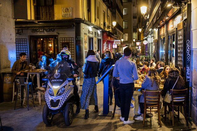 Policeman patrols in downtown Madrid, Spain, Friday, March 26, 2021. With its policy of open bars and restaurants — indoors and outdoors — and by keeping museums and theaters running even when outbreaks have strained hospitals, Madrid has built a reputation as an oasis of fun in Europe's desert of restrictions. Other Spanish regions have a stricter approach to entertainment. Even sunny coastal resorts offer a limited range of options for the few visitors that started to arrive, coinciding with Easter week, amid a set of contradictory European travel rules. (Photo by Bernat Armangue/AP Photo)