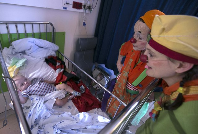 Belgian clowns Rondelle (C) and Bretzel (R) interact with six-month-old baby Lucas, who is hospitalized at the pediatric department of the Hopital Erasme at the Universite Libre de Bruxelles (ULB), in Brussels  February 10, 2015. (Photo by Yves Herman/Reuters)