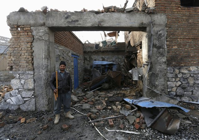 """An Afghan policeman stands guard at the gate of a French restaurant  """"Le Jardin"""" after a suicide attack in Kabul, Afghanistan January 2, 2016. (Photo by Mohammad Ismail/Reuters)"""