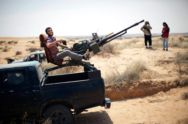 A rebel fighter rests on a weapon mounted on the back of a pickup truck on the front line between them and Muammar el-Qaddafi forces, 30 km south of Misurata, on May 27, 2013. (Photo by Rodrigo Abd/AP Photo)