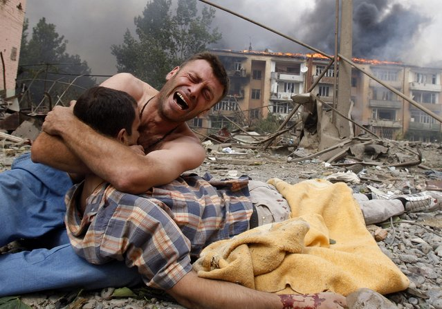 A Georgian man cries as he holds the body of his relative after a bombardment in Gori, Georgia, August 9, 2008. (Photo by Gleb Garanich/Reuters)
