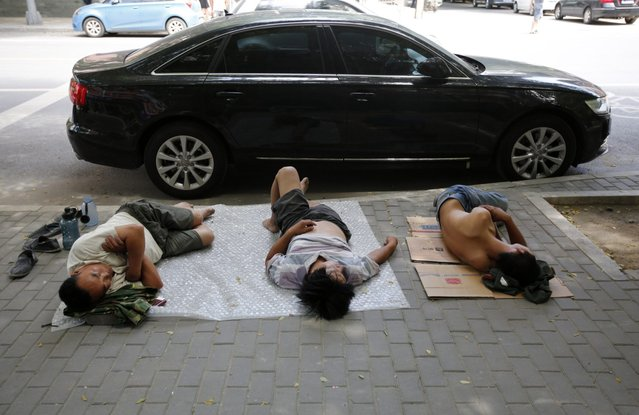 People take a nap on a street in Beijing July 4, 2013. (Photo by Kim Kyung-Hoon/Reuters)