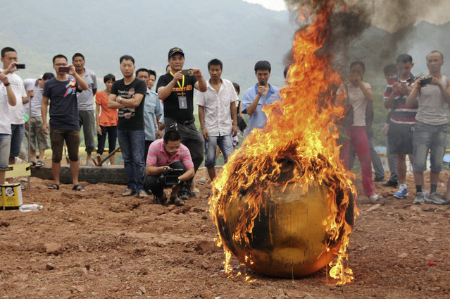 A smaller version of Noah's Ark of China, a six-ton (5,443 kg) ball container built by Chinese inventor Yang Zongfu, undergoes a burning test in Yiwu, Zhejiang province, August 6, 2012. According to local media, Yang spent two years and 1.5 million RMB (235,585 USD) to build the four-metre diameter vessel, which has been tested capable of housing a three-person family and sufficient food for them to live in 10 months. The vessel was designed to protect people inside from external heat, water and external impact. (Photo by Reuters/China Daily)
