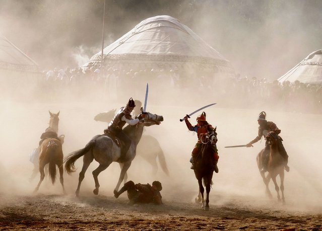 Horsemen fight through clouds of dust during a simulated battle as part of the kickoff. (Photo by Amos Chapple/Radio Free Europe/Radio Liberty)