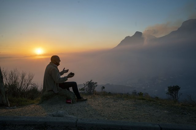 A Capetonian watches the sun rise from the top of Signal Hill as smoke engulfs the city of Cape Town, South Africa, Tuesday April 20, 2021. A massive fire spreading on the slopes of the city's famed Table Mountain, at right, is kept under control as firemen and helicopters take advantage of the low winds to contain the blaze. (Photo by Jerome Delay/AP Photo)