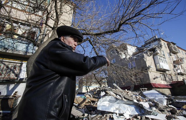 A local resident points at a house damaged by a shelling in the town of Dokuchayevsk, south of Donetsk, February 12, 2015. (Photo by Maxim Shemetov/Reuters)