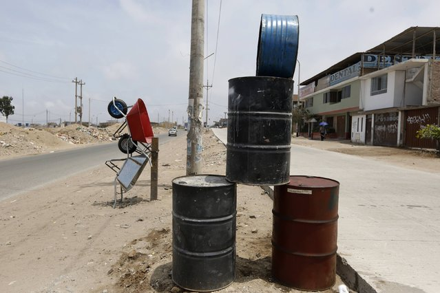 Empty oil barrels that are for sale are stacked outside a  hardware store in Villa El Salvador on the outskirts of Lima, February 12, 2015. (Photo by Mariana Bazo/Reuters)