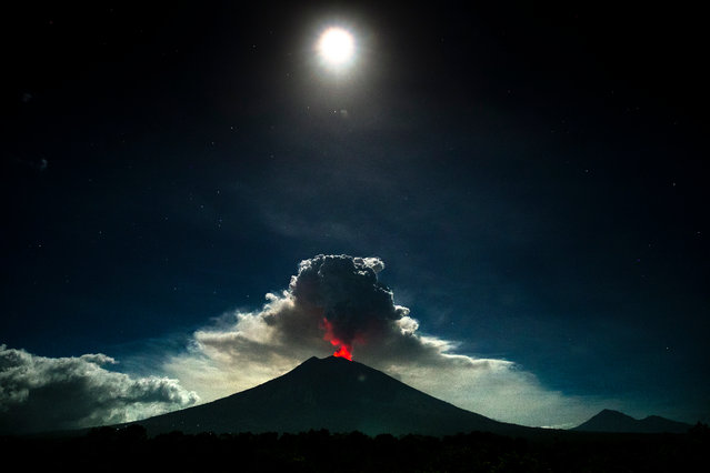 Mount Agung volcano spews hot volcanic ash into the air as seen from Kubu Village in Karangasem, Bali, Indonesia, 29 June 2018. The ash cloud out of Mount Agung was reported to have reached a height of 2000 m after it began to erupt on the evening of 28 June. The Ngurah Rai International Airport in Bali was shut down at 03.00 am on the 29 June 2018 due to hazards related to the ash cloud. (Photo by Made Nagi/EPA/EFE)