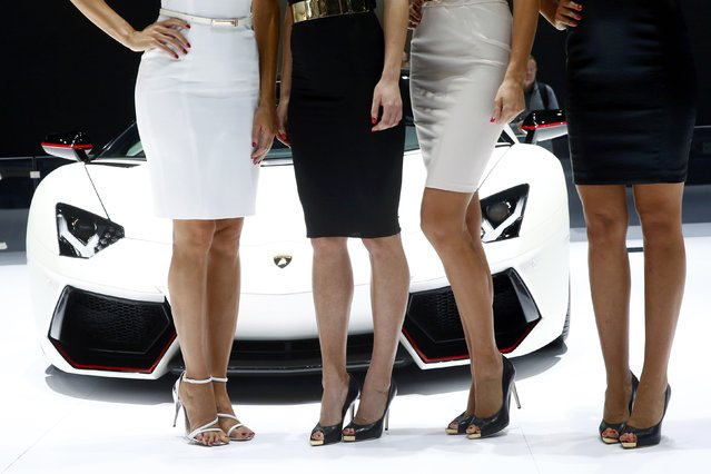 Models pose in front of a Lamborghini Aventador LP 700-4 during the second press day ahead of the 85th International Motor Show in Geneva March 4, 2015.  REUTERS/Arnd Wiegmann