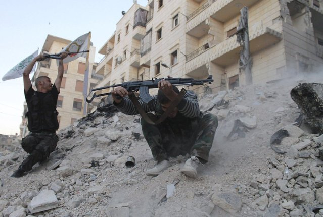 """""""Free Syrian Army"""" fighters fire their weapons during what the FSA said were clashes with forces loyal to Syria's President Bashar al-Assad in Aleppo's Karm al-Jabal district October 15, 2013. (Photo by Saad Abobrahim/Reuters)"""