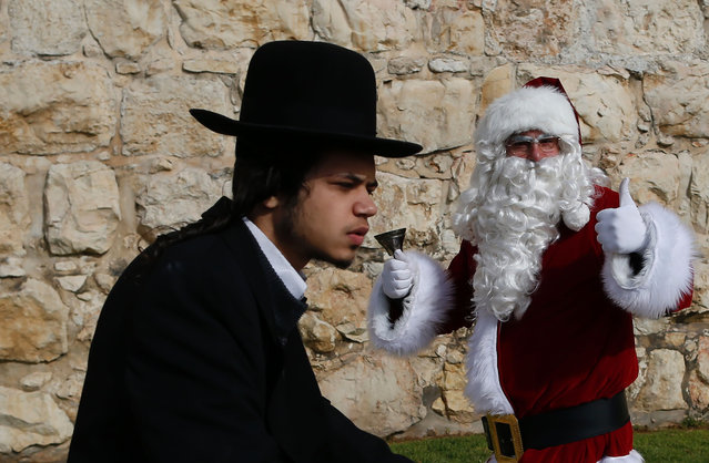An Ultra- Orthodox Jew rides past a Palestinian man dressed up as Santa Claus outside Jaffa Gate in Jerusalem' s Old City, on December 23, 2016, as Christians around the world prepare to celebrate the holy day. (Photo by Ahmad Gharabli/AFP Photo)