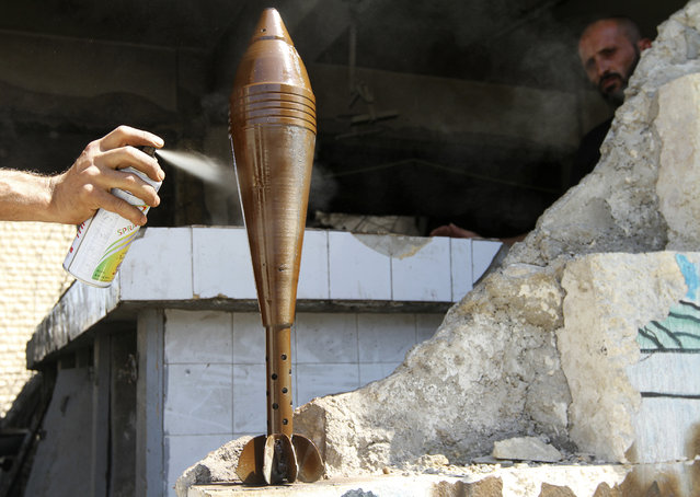 A Free Syrian Army fighter spray paints an improvised mortar shell, as his fellow fighter watches him, in Aleppo September 4, 2013. (Photo by Hamid Khatib/Reuters)